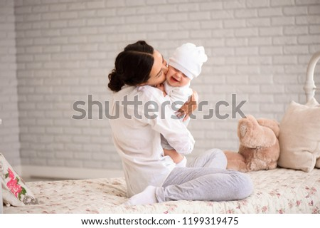 e14d1636e ... wearing knitted trendy winter clothes posing over white brick · Mother,  playing with her toddler boy smiling #1199319475