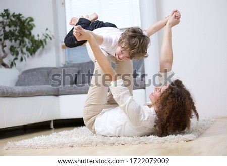 Mother playing with son on rug in living room