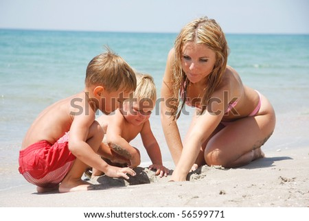 mother playing with two kids on beach