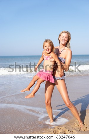 Mother playing with young girl on beach