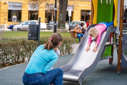 Mother plays with little girl on a playground in Sofia, Bulgaria