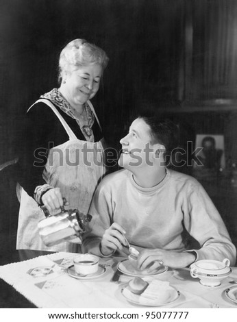Mother pouring coffee for teenage son