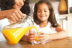 Mother pouring fresh orange juice from a jug for her daughter seated at a wooden table in the kitchen