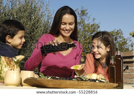 mother pouring olive oil on bread - stock photo