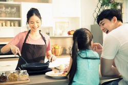 Mother preparing meal for her daughter and husband in the kitchen, concept happy family at dining table