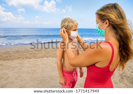 Mother put medical mask on child on sea beach. New rules to wear cloth face covering at public places. Cancelled cruise, tour due coronavirus COVID 19. Family vacation, travel lifestyle at summer 2020