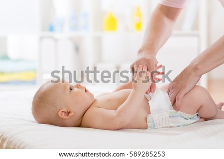 Mother putting diaper on her happy baby in nursery
