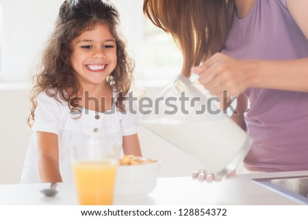 Mother putting milk in the cereal of his daughter in kitchen