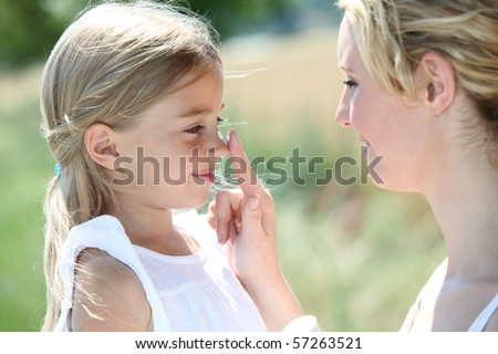Mother putting sunscreen on her daughter's nose
