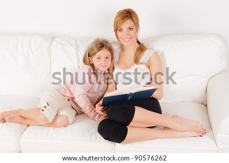 Mother reading a book with her daughter on white sofa