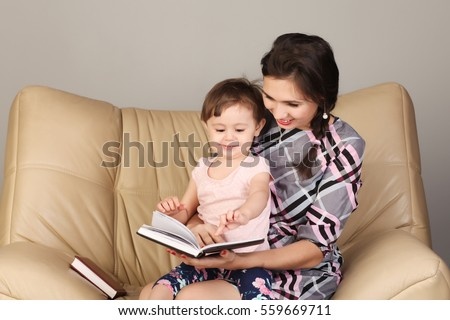 Mother reading a book with her little daughter #559669711