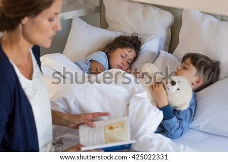 Mother reading bed time stories to children. Brother and sister sleeping peacefully. Mother putting son and daughter to sleep. Stock photo ©