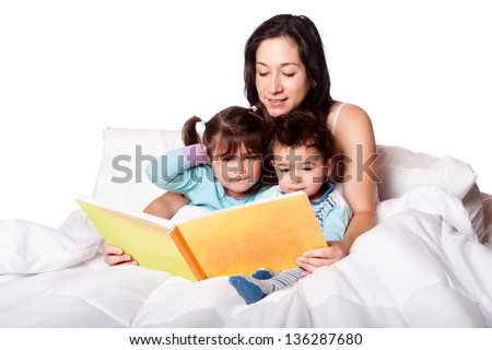 Mother reading bed time story book to daughter and son kids in bed isolated