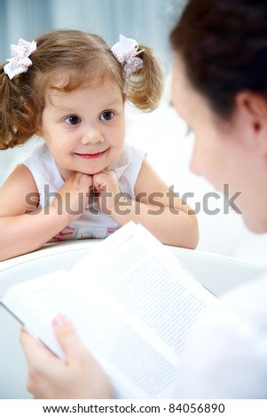 Mother reading book her cute little girl at home