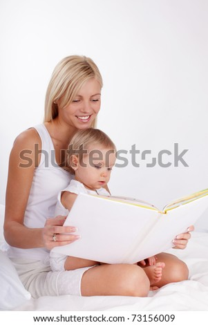 Mother reading book to a daughter at home