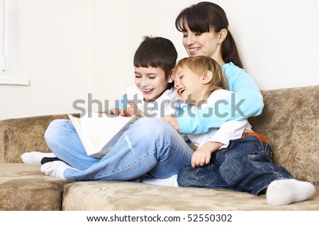 mother reading book to her sons; indoor