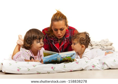 Mother reading story to her kids in bed before sleep