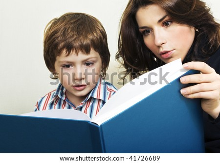 Mother reading to her son interesting story. Real emotions. - stock photo