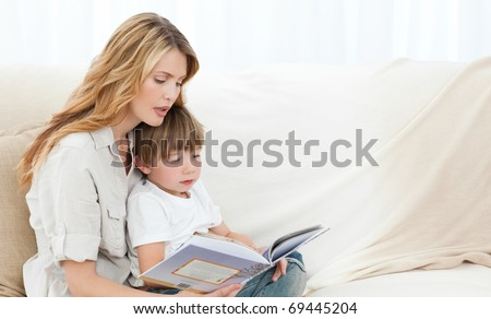Mother reading with her son on the sofa