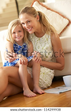 Mother Relaxing At Home With Daughter