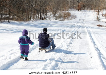 Mother rides a sled, as a child running behind it - stock photo
