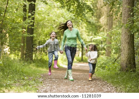 Mother running along woodland path with 2 childrren