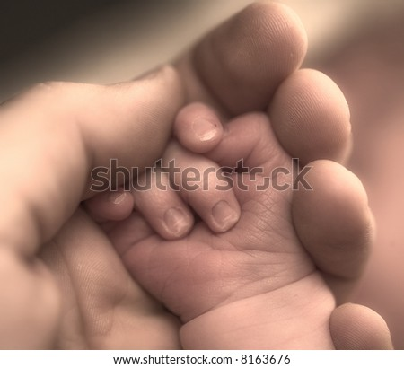Mother's and baby's hands - sepia