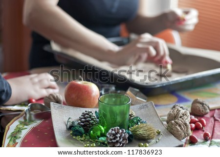 Mother's and son's hands going to the Christmas table