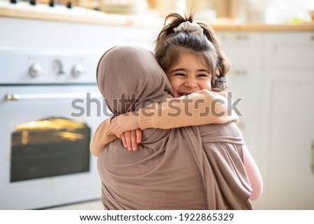 Mother's Day Concept. Cheerful Little Girl Hugging Tight Her Muslim Mom In Hijab, Islamic Woman Embracing Smiling Female Child, Happy Family Bonding Together In Kitchen At Home, Copy Space