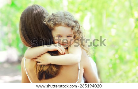 Mother\'s day, family, childhood and people concept - happy daughter hugging mother in warm sunny summer day on the nature