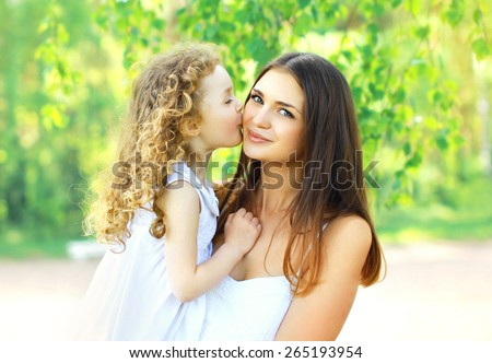 Mother\'s day, family, childhood and people concept - loving daughter kissing mother, happy young mom and child in warm sunny summer day on the nature