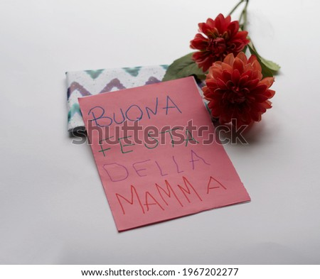 """Mother's Day gifts. Flowers, a present and handmade greeting card with message in Italian """"Buona festa della mamma"""". Isolated in white background. Maternity, Love, Motherhood Stockfoto ©"""