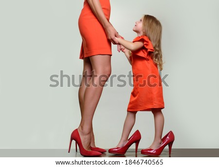 Mother's day. Girl dreaming about fashionable high heels. Shoes shop. Wish to grow up faster. Child support. Kids care concept. Relationship of mother and daughter Stock photo ©