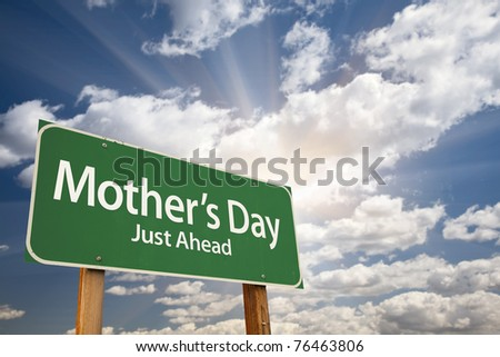 Mother's Day Green Road Sign on Dramatic Blue Sky with Clouds.