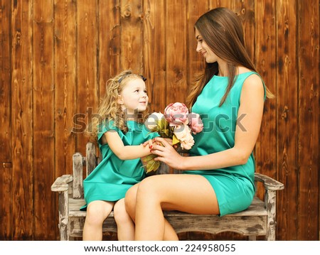 Mother\'s day, holiday, christmas, birthday concept - beautiful mother and daughter, little girl gives bouquet flowers mother