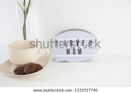 Mother's day.  I love you MOM written at the white oval word board with the carnation flowers and a cup of coffee serve with cookies over the white background #1332927740
