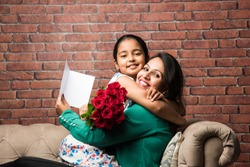 Mother's Day - Indian girl / mother celebrating Mother's day with Rose Flower Bouquet, greeting card while hugging and kissing each other