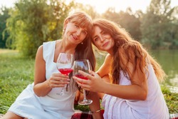 Mother's day. Mother drinking wine with her adult daughter in spring park. Family having picnic outdoors. Women spending time together
