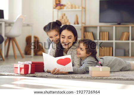 Mother's Day. Twin sisters hug and greet their mother by giving her a handmade card and gifts. Excited happy mother lying on the floor with children and reading greetings. Concept of family and love.