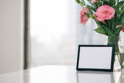 Mother's Day, Women's Day or other suitable holiday card in rectangular photo frame with blank space for your text on white table with Lisianthus flowers bouquet in glass bottle and paraffin candle