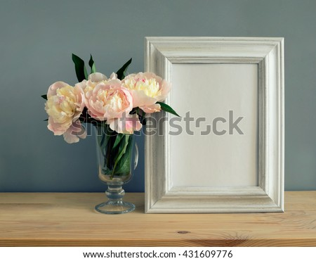Mother's Day, Women's Day or other suitable holiday card, photo frame with blank space for a text on a table with flowers bouquet, stylized image