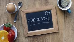 Mother's day written in Dutch on a chalkboard between a breakfast for her