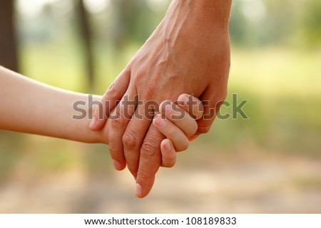 mother\'s hand lead her child son in summer forest nature outdoor, trust family concept