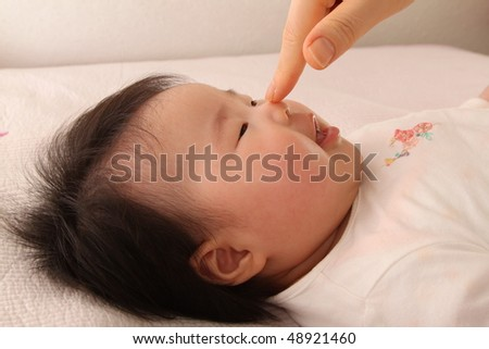 Mother's hand touching cute asian baby girl on her button nose