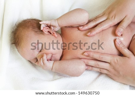 Mother's hands massaging cute baby having colic.