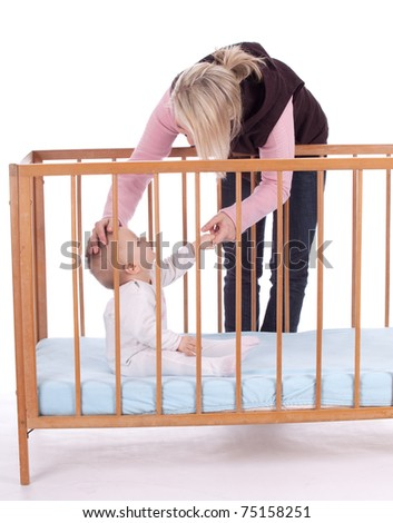 mother's love -  cute baby 7  month boy in cot with mother