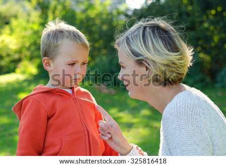 Mother scolds her son crying in the park