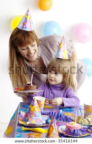 mother serving cake at childrens birthday party