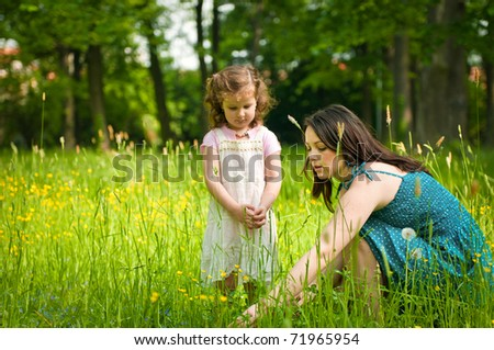 Mother shows with finger to her cute little daughter something interesting in grass
