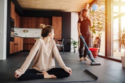 Mother sits at easy simplified lotus pose, looking at the father vacuum cleaning apartment floor with their infant baby riding on his neck. Family quarantine, domestic life in self-isolation.